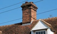 Mortar fillets are commonly used at the junction between peg tiles and a chimney (shown above), but lead flashings (shown here) are much more reliable.